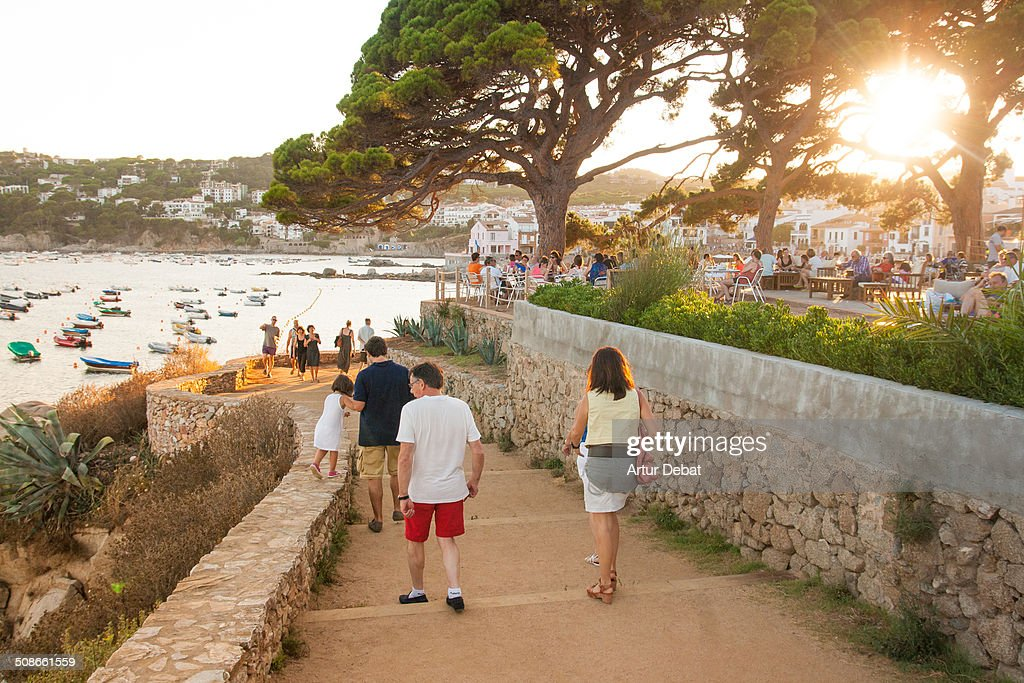 Family walking through the beach boardwalk at sunset with warm light in the Costa Brava shoreline Catalonia Europe