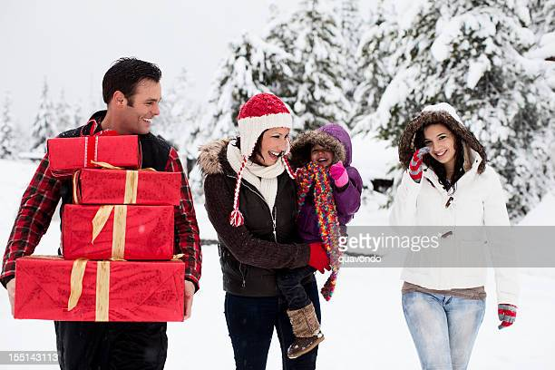 Adorable Family Walking in Winter Snow with Christmas Presents