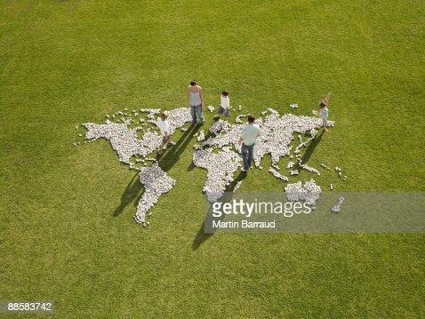 Family walking through world map made of rocks : Stock Photo