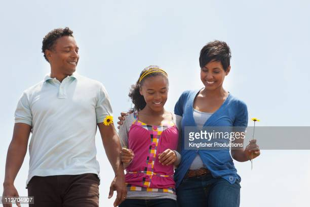 Family walking together holding flowers
