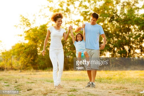 Family walking together in field at sunset