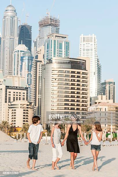 Family walking together on beach, Dubai, United Arab Emirates
