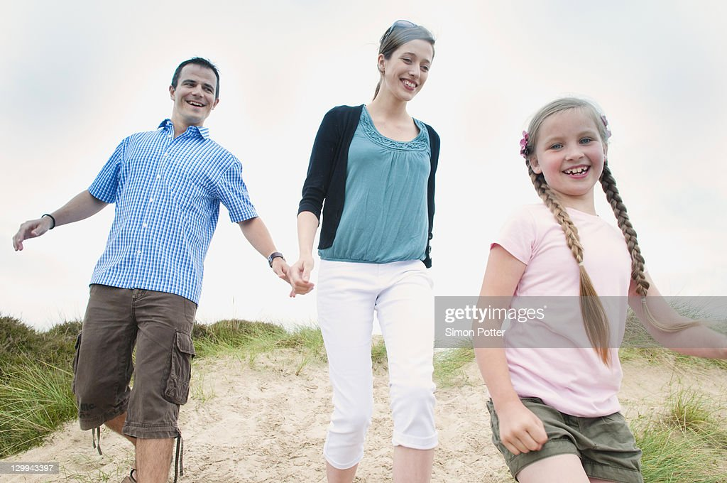 Family walking together on beach : Stock Photo