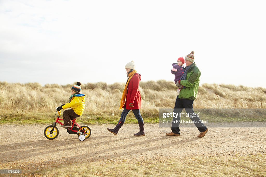 Family walking together on rural road : Stock Photo