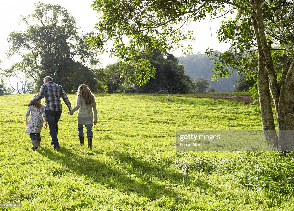 Family walking up a grassy hill together  : Stock Photo