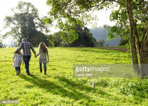 Familie gehen zusammen auf einem grasbewachsenen Hügel : Stock-Foto