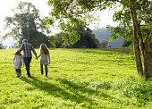 Familie gehen zusammen auf einem grasbewachsenen Hügel