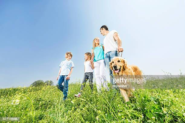 Family walking with a golden retriever in nature.