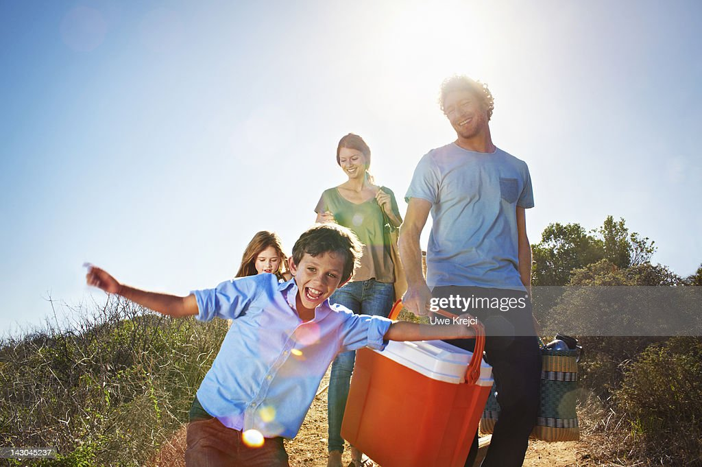 Family walking with picnic paraphernalia in park : Stock Photo