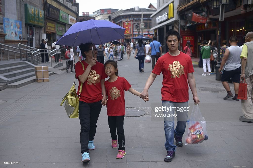 A family walks along a business street in Beijing on June 1, 2016. Activity in Chinese factories expanded for the third straight month in May, official data showed, a further sign of stabilisation in the world's second largest economy.The official Purchasing Manager's Index (PMI), which tracks activities in the country's factories and workshops, came in at 50.1 on June 1, according to the National Bureau of Statistics (NBS). / AFP / WANG