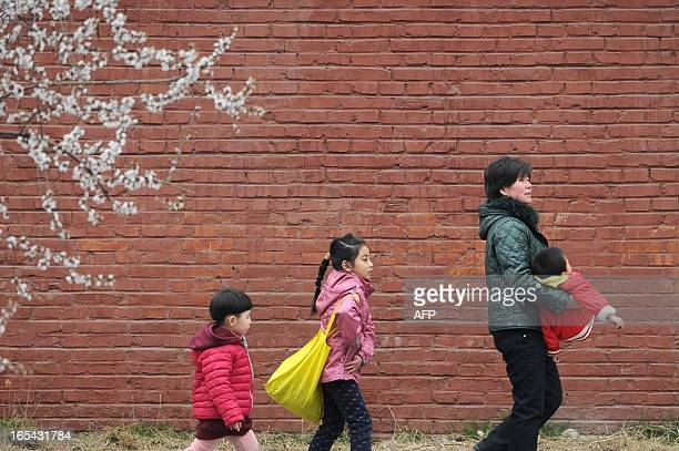 A family walks along a street in Beijing on April 42013 Spring has arrived in the city bringing with it the peak tourist season and tens of thousands...