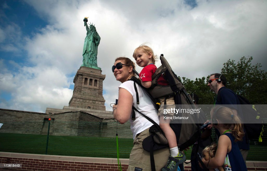 A family walks by the Statue of Liberty on the first day it is open to the public after Hurricane Sandy on July 4, 2013 on the Liberty Island in New York City. The statue was mostly spared by the storm, but the surrounding infrastructure was badly damaged.