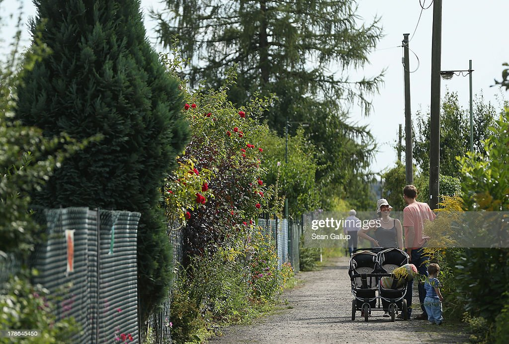 A family walks down a path at the Oeynhausen Small Garden Association garden colony on August 29, 2013 in Berlin, Germany. At the Oeynhausen colony about 300 of its 438 gardens are currently threatened by real estate development, as are about another 24 colonies across the city. Berlin has about 900 garden colonies that are owned by the city and that provide urban dwellers who don't have land of their own the opportunity to maintain a garden and escape the stress of urban life. Berlin is currently undergoing a housing squeeze and city authorities are beginning to sell some of the colonies to developers, which has caused outrage in a city where the colonies of small gardens are a deep-seated tradition going back over a century.
