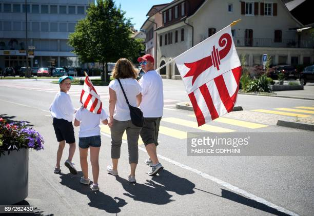A family walks in the city's main street with a flag of the Jura canton during an historical anticipated vote on June 18 2017 in Moutier northern...
