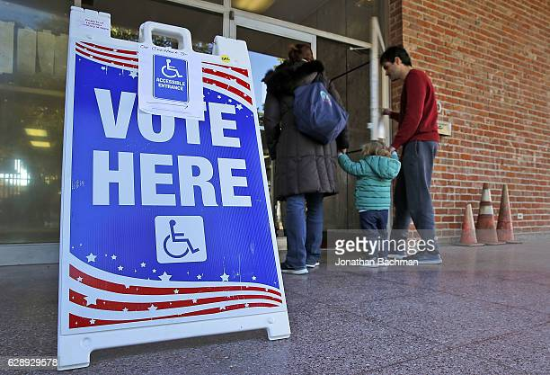 A family walks into a polling station on December 10 2016 in New Orleans Louisiana Louisiana residents head to the polls on Saturday to select a US...