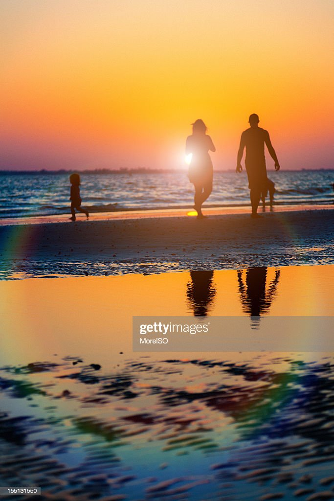 Family Walks on the Beach at Sunset