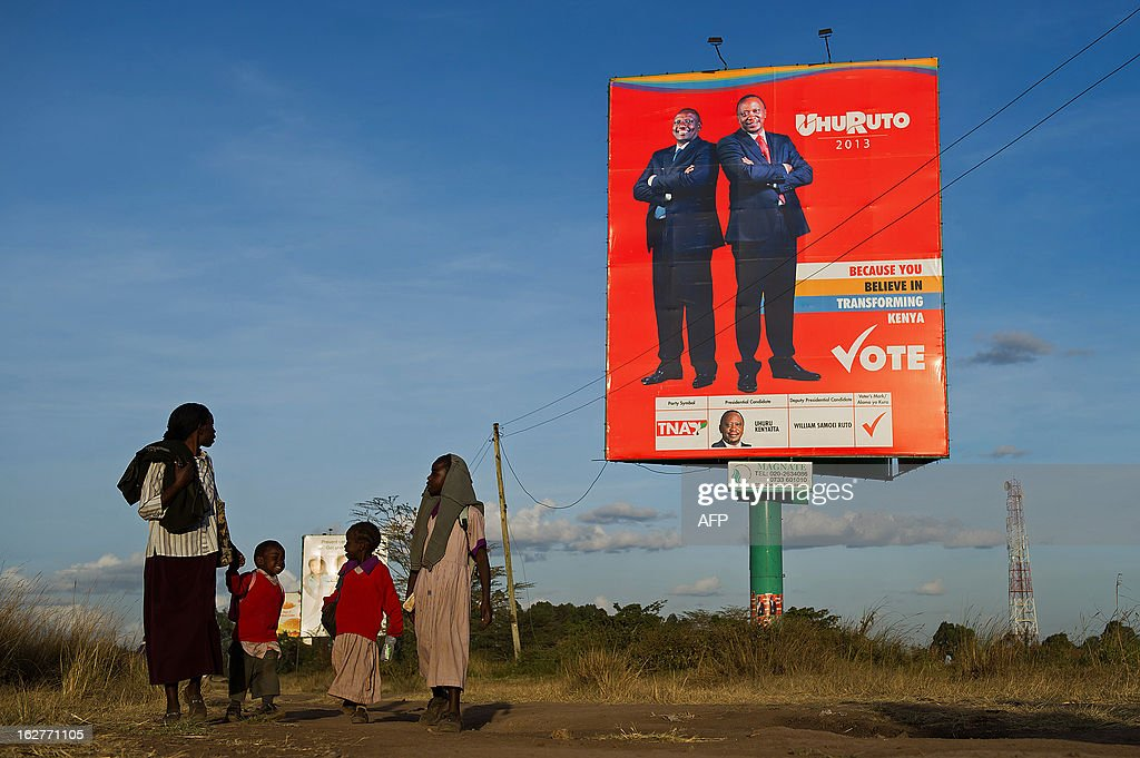 A family walks past a large billboard campaigning for presidential candidate Uhuru Kenyatta and his running-mate William Ruto on the outskirts of Nairobi, Kenya on February 26, 2013. Kenya is gearing up for presidential, national elections on March 4, the first since bloody post-poll violence five years ago in which more than 1,100 people died after contested results.
