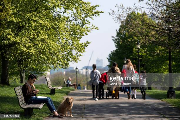 A family walks past a man and his dog on Primrose Hill in the sun on April 7 2017 in London England Temperatures are predicted to rise to 23 degrees...