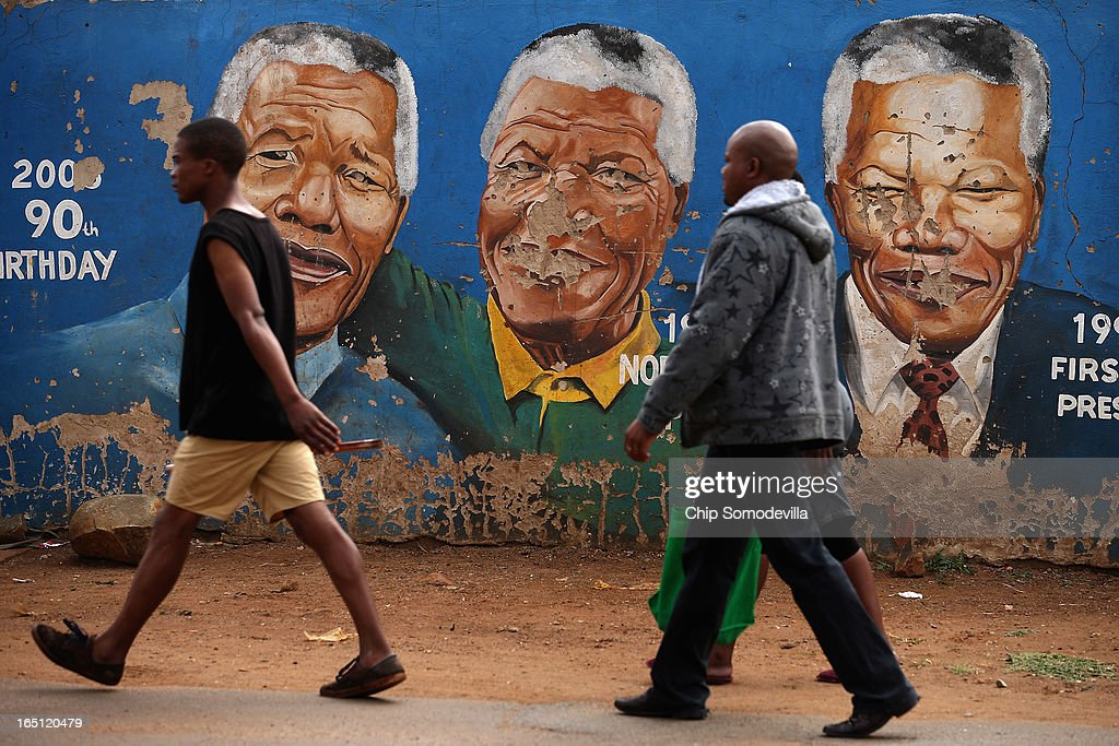 A family walks past a mural depicting former South African President Nelson Mandela during different times in his life near the Regina Mundi Catholic Church in the Soweto area March 31, 2013 in Johannesburg, South Africa. A central gathering place during he anti-apartheid struggle, the church held prayers for Mandela, 94, who is in the hospital for the third time since December with lung problems. Referring to Mandela by clan name, Madiba, President Jacob Zuma said, 'We appeal to the people of South Africa and the world to pray for our beloved Madiba and his family and to keep them in their thoughts.' Mandela's lungs were damaged when he contracted tuberculosis during his 27 years in the infamous Robben Island prison. Mandela became the nation's first democratically elected president in 1994 following the end of apartheid.