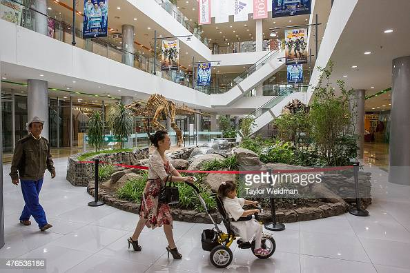 A family walks past dinosaur skeletons displayed in the new Hunnu Mall on June 10 2015 in Ulaanbaatar Mongolia A few years ago Mongolia boasted one...