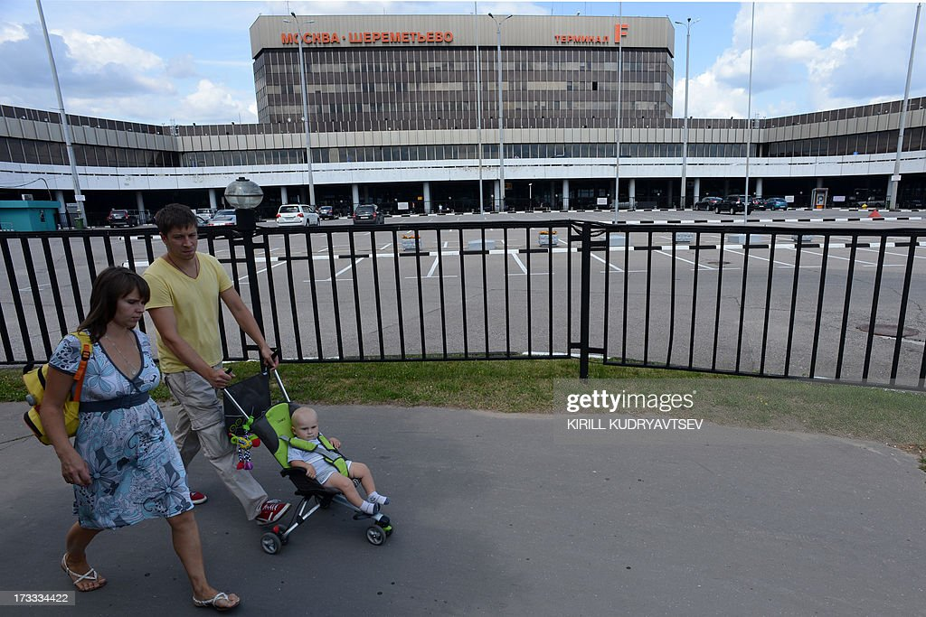 A family walks past the terminal F of Moscow's Sheremetyevo airport, on July 12, 2013, where US National Security Agency (NSA) fugitive leaker Edward Snowden reportedly remains without making any contact with the swarm of international reporters at the scene. Snowden has requested a meeting with leading Russian rights activists and lawyers at the airport in Moscow where he has been stuck in transit for the last three weeks, the campaigners invited said today.