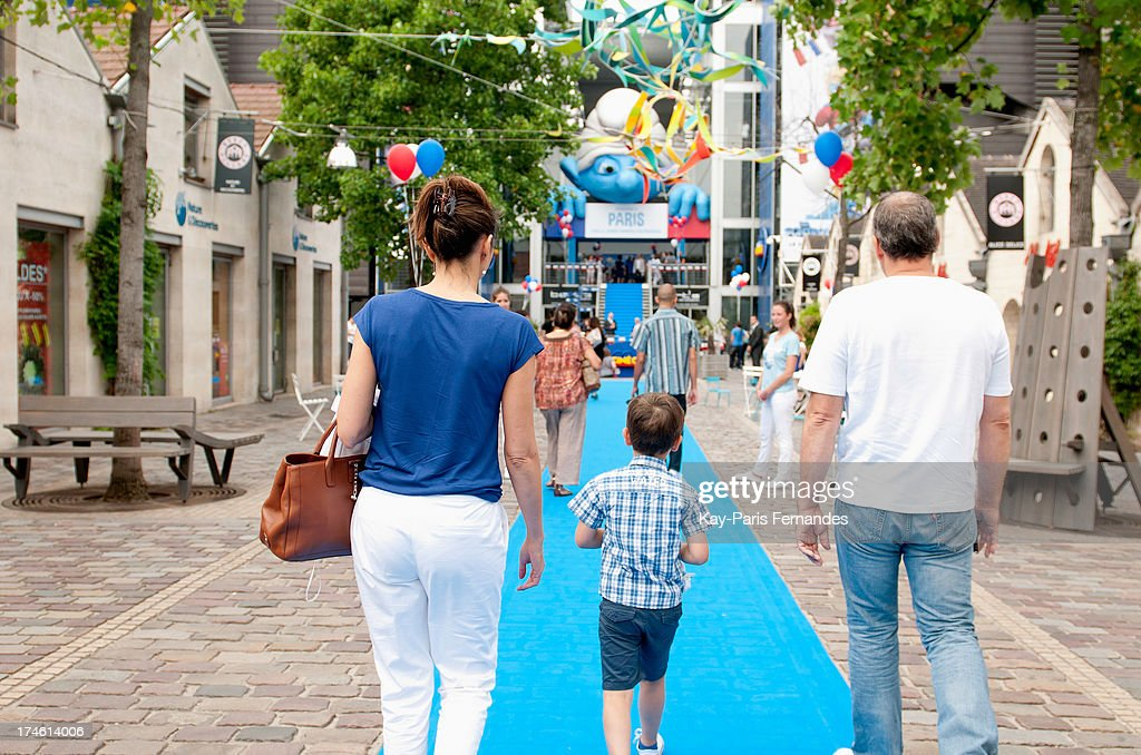 A family walks the blue carpet to the entrance of the 'Smurfs 2' Paris Premiere at UGC Cine Cite Bercy on July 28, 2013 in Paris, France.