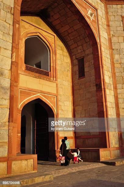 A family walks through the main gate at Humayun's Tomb, Delhi, India