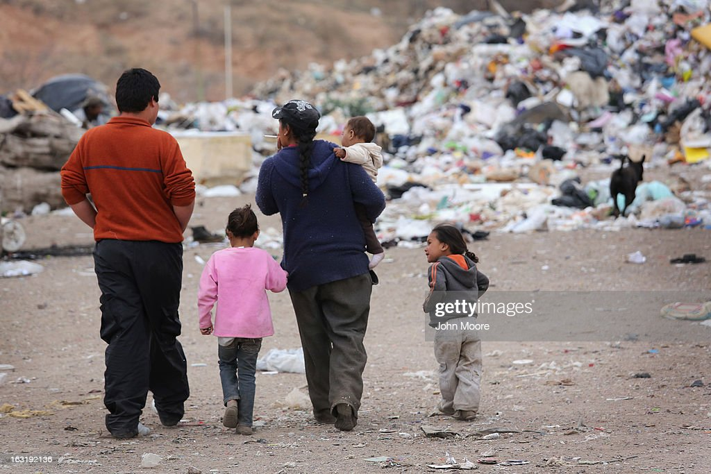 A family walks through the Tirabichi garbage dump on March 5, 2013 in Nogales, Mexico. About 30 families live at the landfill, searching for recyclables to sell for a living. Some residents there were undomumented immigrants who were caught and deported by the United States back to Mexico. While living at the dump, they have received aid from the non-profit Home of Hope and Peace, which plans to expand its assistance to the dump's impoverished populace in the future.