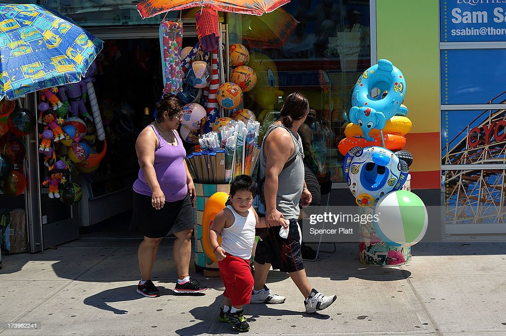 A family walks to the Coney Island boardwalk on one of the hottest weeks in recent New York City history on July 18, 2013 in New York City. With daily temperatures in the high 90's and with the heat index making it feel in the triple digits, many New Yorkers are doing what they can to stay cool. A break from the heatwave is not expected until Saturday evening at the earliest.