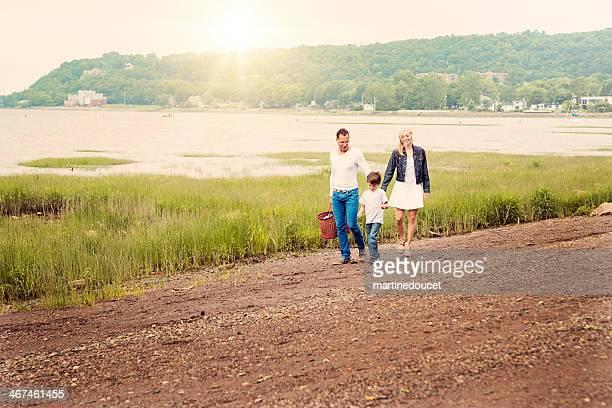 Interracial famille marchant avec panier de pique-nique sur une plage du nord.
