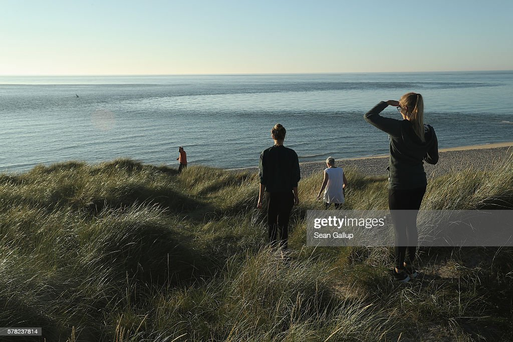 A family walks towards the beach at sunset near the northern end of Sylt Island on July 19, 2016 near List, Germany. Sylt Island, with its long stretches of sand beaches and its protected dune landscapes, is among the most popular holiday destinations, especially for wealthy visitors, along Germany's North Sea coast. Many Germans, unsettled by the recent terror attacks in countries like France and Turkey, are choosing to vacation in Germany this summer.
