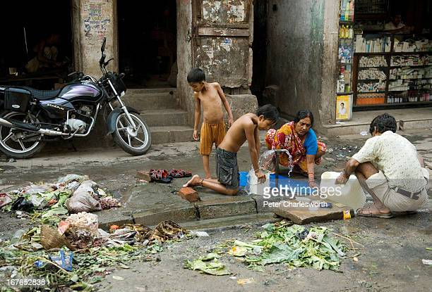 A family washes with water from a kerbside tap next to a pile of garbage on a Kolkota street