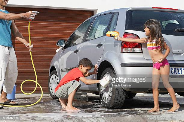 Family washing car and having water fight