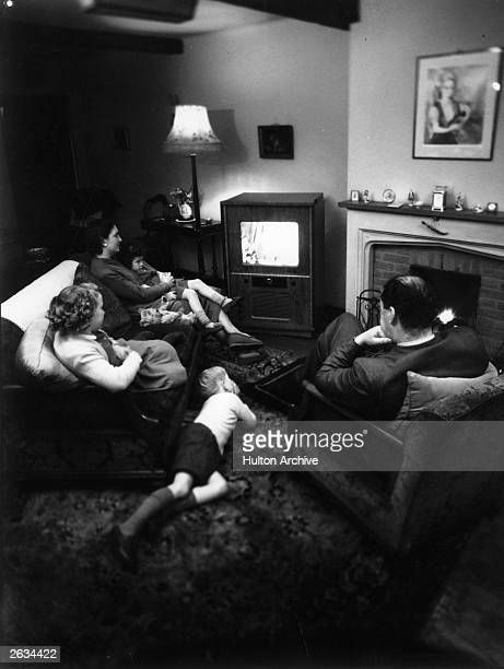 A family watch colour television in their sitting room
