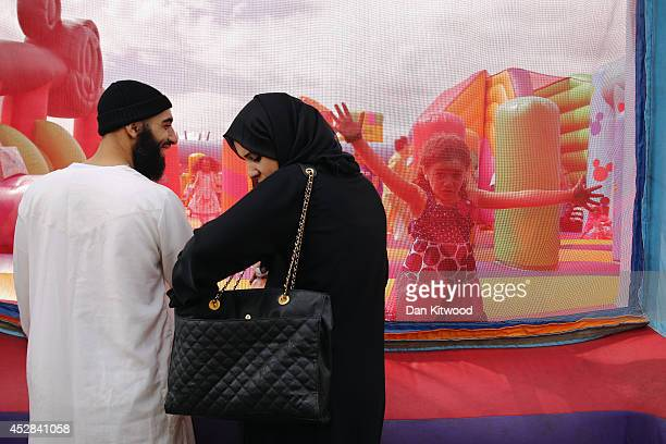 A family watch their children on a bouncy castle during an Eid celebration in Burgess Park on July 28 2014 in London England The Muslim holiday Eid...