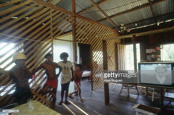 A family watches television in the South American rainforest With the aid of a satellite dish the Brazilian family living in French Guiana can...