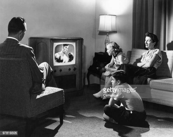 A family watching a boxing match on television in their home circa 1950