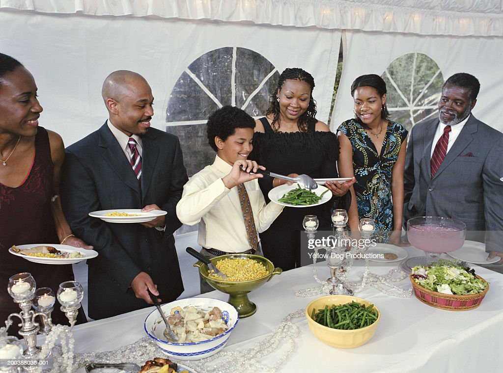 Family watching boy (10-12) filling plate with green beans at party : Stock Photo