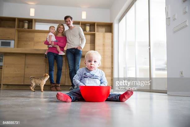 Family watching male toddler with bowl on dining room floor