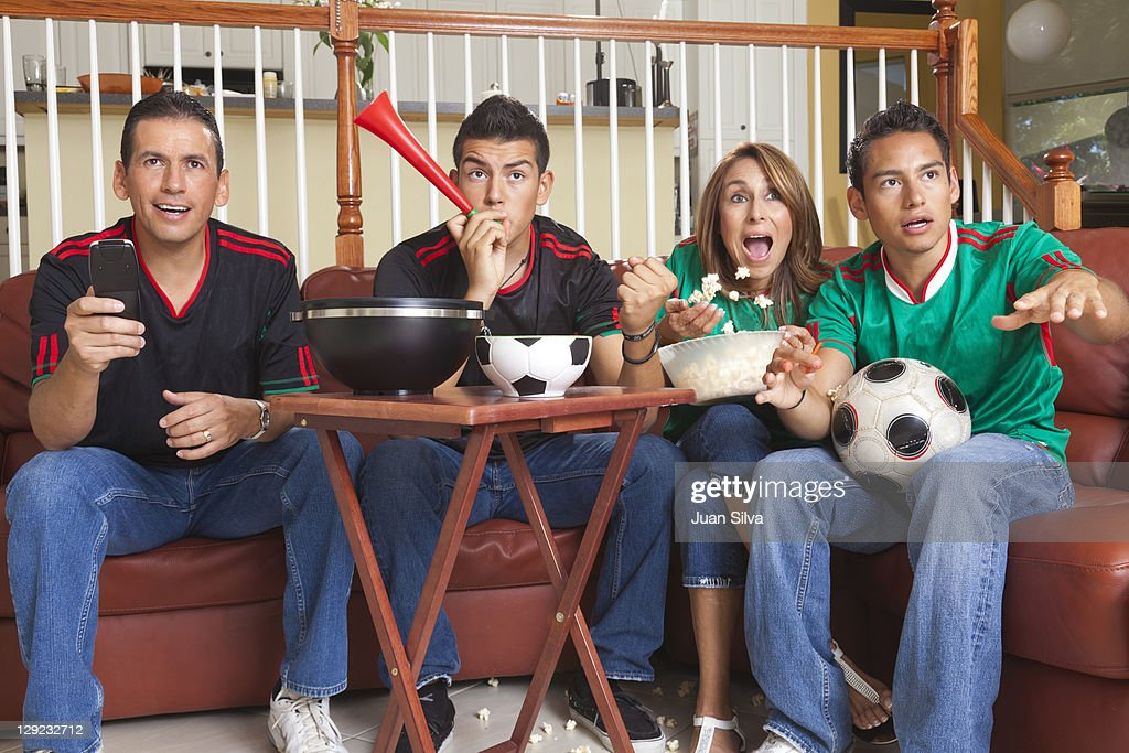 Family watching soccer game on TV : Stock Photo