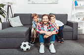 smiling father with adorable little sons watching soccer match together at home