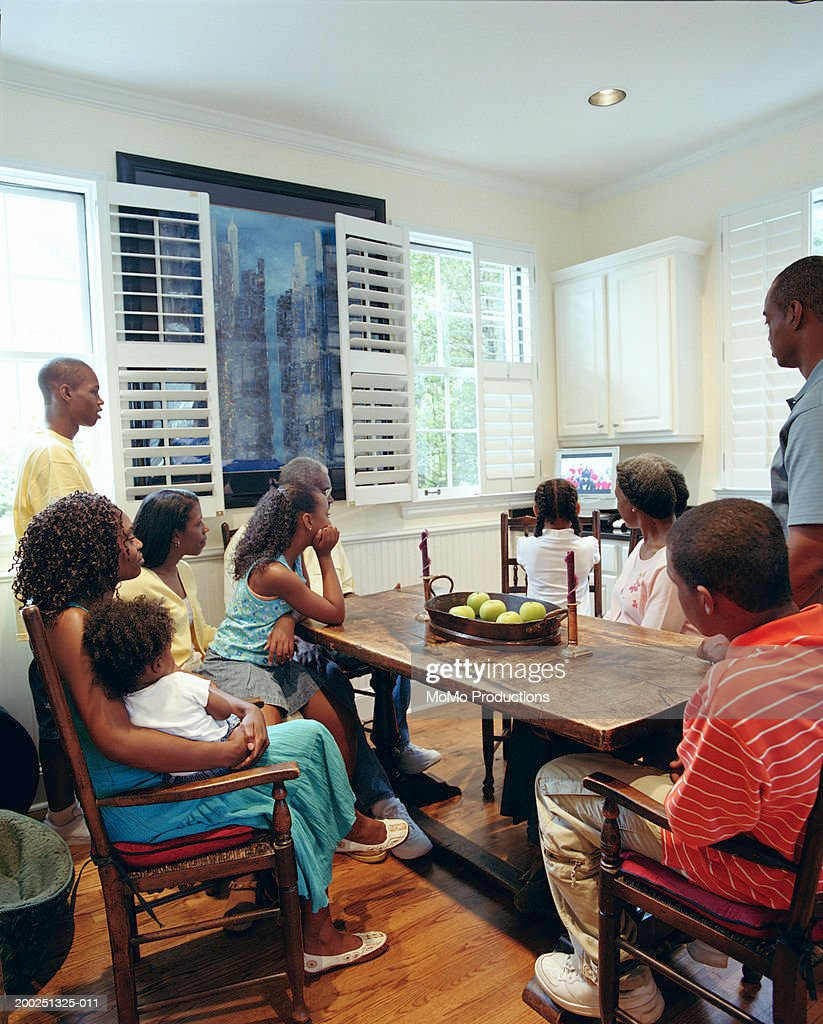 Kitchen Side View : Family watching television in kitchen side view stock
