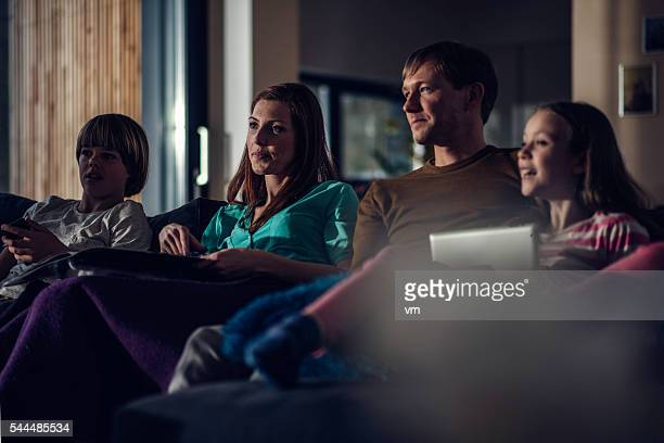 Family watching television in the evening