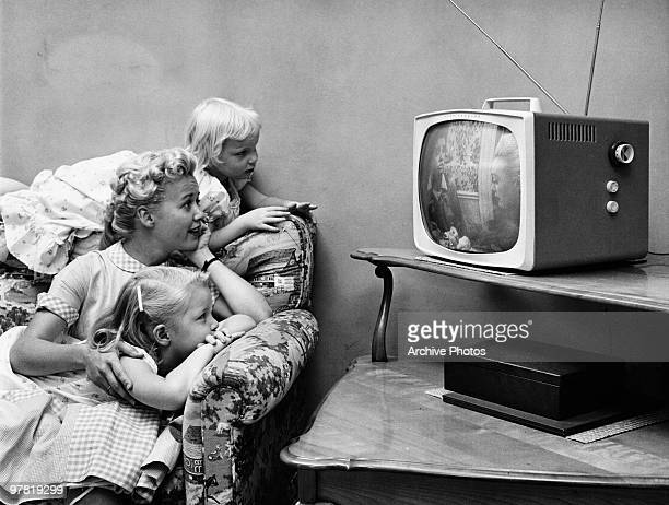 A family watching television in their home circa 1955