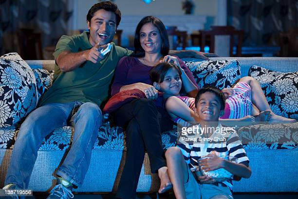 Family watching television, laughing