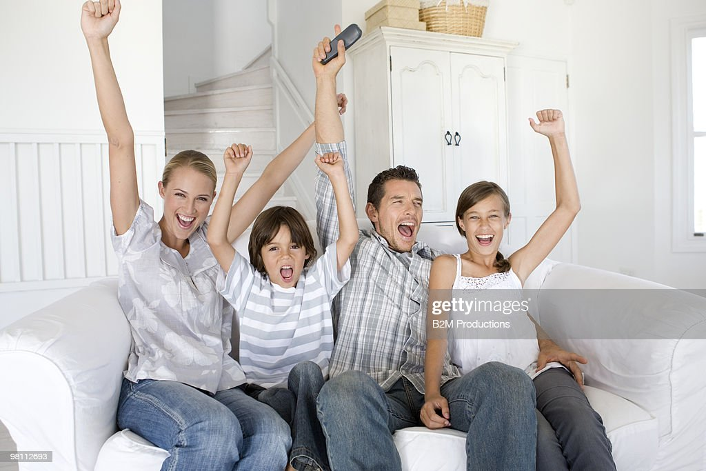 Family watching television together, cheering : Stock Photo