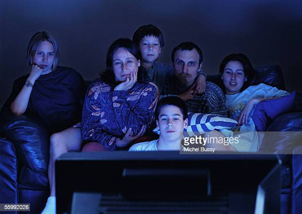 Family watching television together in the dark.