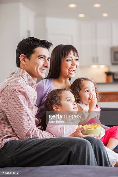 Family watching television together on sofa