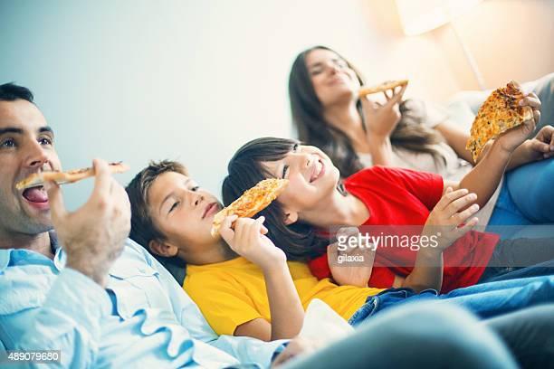 Familia viendo la televisión y comiendo una pizza.