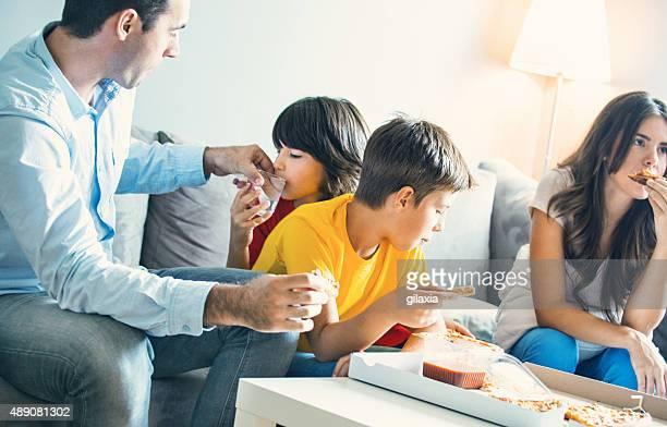 Familie vor dem Fernseher und Essen pizza.